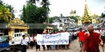 """Protesters marched around Yangon with a banner that reads """"non-violence: national movement in Burmese."""""""