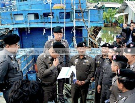 Deputy Police Chief Lieutenant-General Srivara Ransibrahmanakul inspects documents relating to 24 suspected slave fishing boats impounded in Songkhla