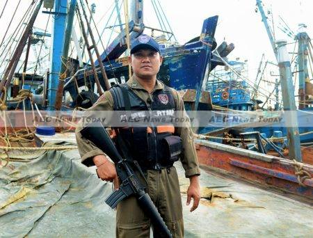 A Royal Thai Marine Police (RTMP) officer stands guard over suspected slave fishing boats impounded in Songkhla, southern Thailand