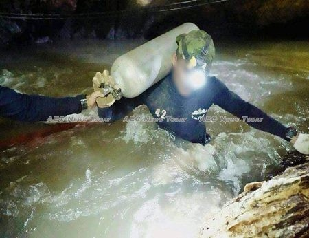 Two Thai Navy Seals battle their way against the current to move diving air tanks deeper into Tham Luang cave