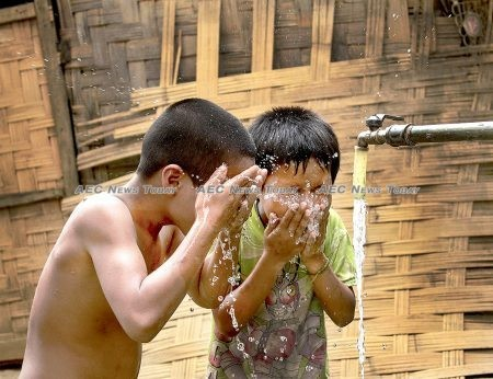 Children cooling off with clean, piped water in Khan Village.