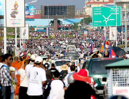 Mourners gather by the roadside as the funeral procession of Kem Ley passes in 2016
