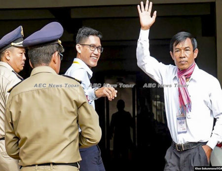 Former RFA journalist Yeang Sothearin waves to journalists and supporters as he enters the Phnom Penh Municipal Court with Uon Chhin