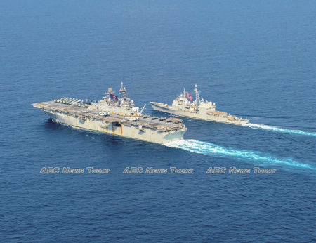The USS America (LHA-6), left, and the guided-missile cruiser USS Bunker Hill (CG-52) navigate the South China Sea on April 18, 2020.