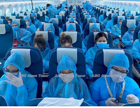 Vietnamese citizens return home on a Vietnam Airlines flight